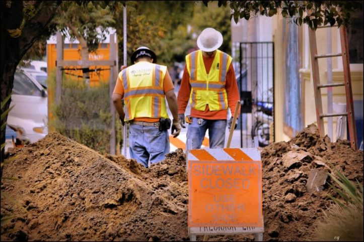 Two San Francisco construction workers peer into a manhole