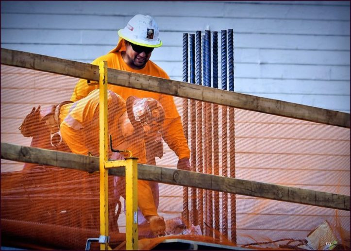 Two construction workers building a roof